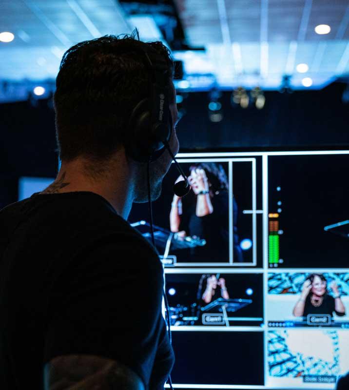 Bild für Livestreaming - Blick über die Schulter einen Person (dunkel) auf einen Regiemonitor