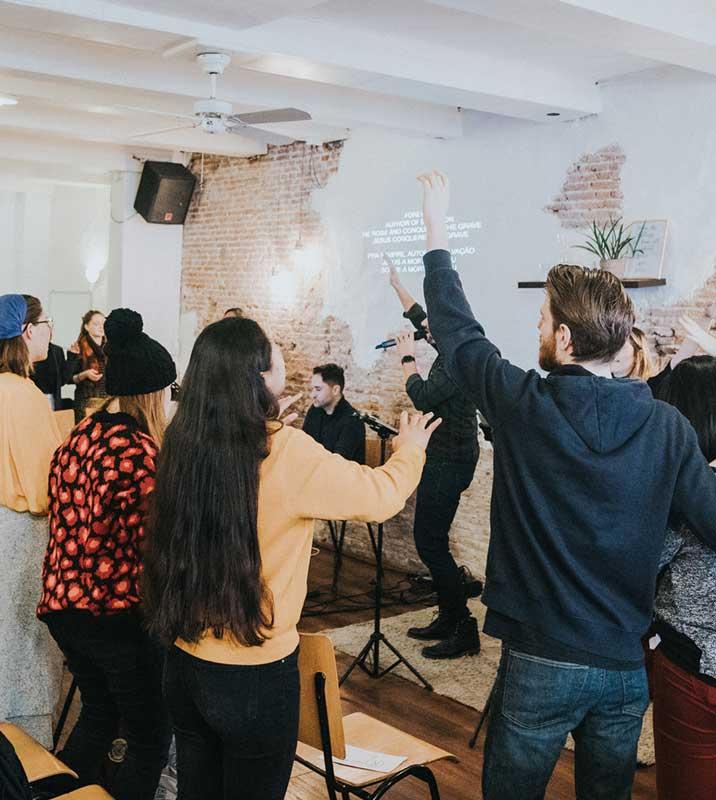 Bild für Livestreaming - Blick in einen charismatischen Gottesdienst (beim Lobpreis) Menschen stehen Sängerin