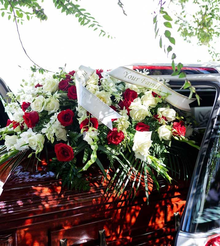 Bild für Stream Trauerfeier - Blumenschmuck liegt über Sarg